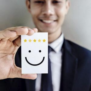 Młody męzczyzna pokazuje kartkę z pięcioma gwiazdkami