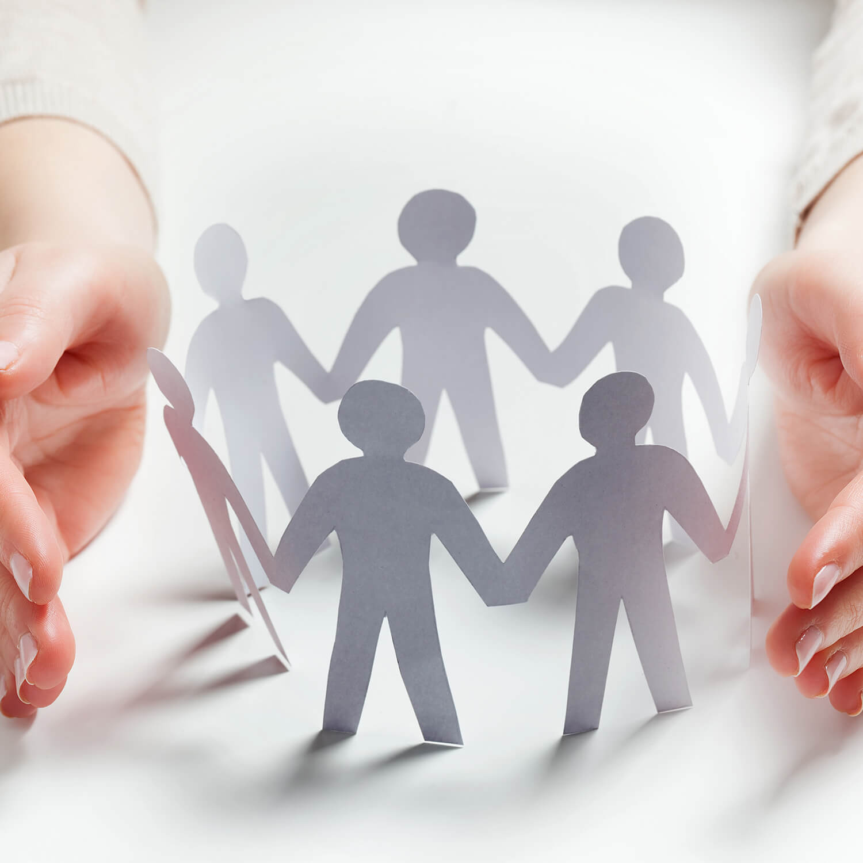 Dłonie otaczają grupę ludzików z papieru