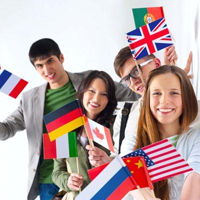 Grupa młodzieży trzymająca w rękach flagi różnych krajów